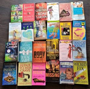 Image features a selection of paperback books, 24 in total, that I bought at my library's Friends of the Library Book Sale